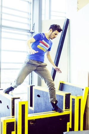 young handsome man doing parkour in gym inside, lifestyle sport people concept