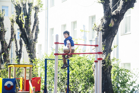 little cute blond boy hanging on playground outside, alone training with fun, lifestyle children concept 스톡 콘텐츠