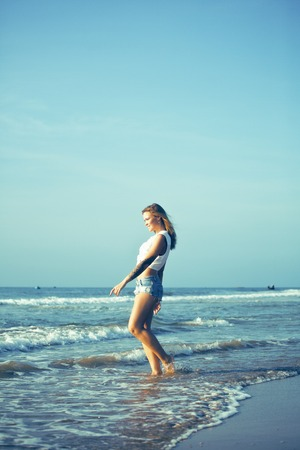 young pretty blond woman at seacoast walking relaxing, fashion lady at sunset, cool vacations 免版税图像