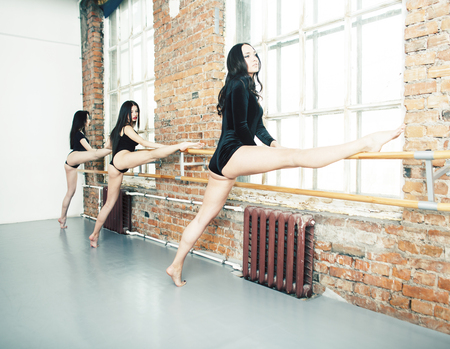 Many girls training in studio ballet, long woman legs sexy bracing, wearing sexual black bodysuit, lifestyle people concept Stock Photo - 125729620
