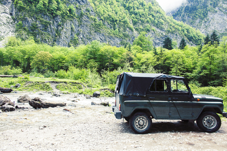 jeep on road hight in mountain, beautiful summer landscape with river close up