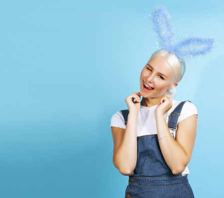 young pretty blond girl with rabbit ears posing cheerful on blue background, lifestyle people concept