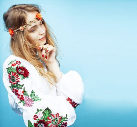 young pretty blond girl posing on blue background, fashion style hippie boho flowers on head Archivio Fotografico