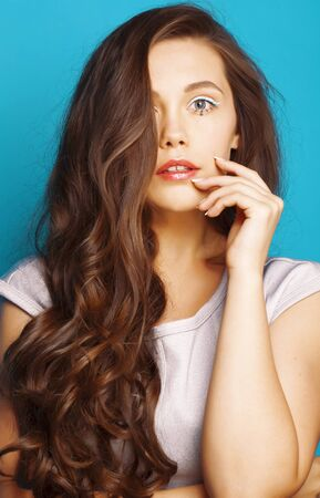 young pretty teenage modern girl posing emotional happy on blue background, lifestyle people concept 스톡 콘텐츠