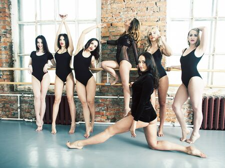 Many girls training in studio ballet, long woman legs sexy bracing, wearing sexual black bodysuit, lifestyle people concept