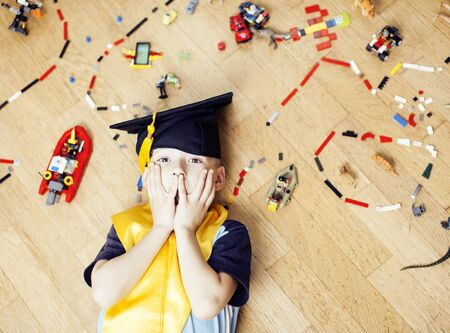 little cute preschooler boy playing toys at home happy smiling in graduation hat, lifestyle children , world map with pieces, self education concept
