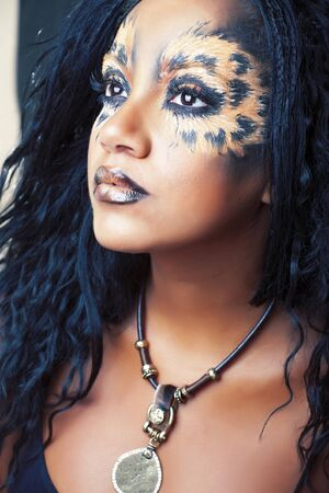 beauty afro girl with cat make up, creative leopard print closeup, fashion style halloween look 免版税图像