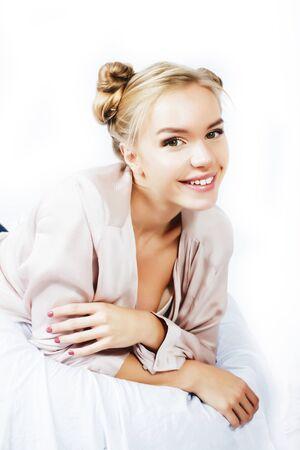 jonge mooie blonde vrouw in bed bedekt witte lakens glimlachend vrolijk, levensstijl mensen concept close-up