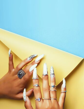 woman hands holding colorful paper copyspace wearing a lot of jewelry and long nails