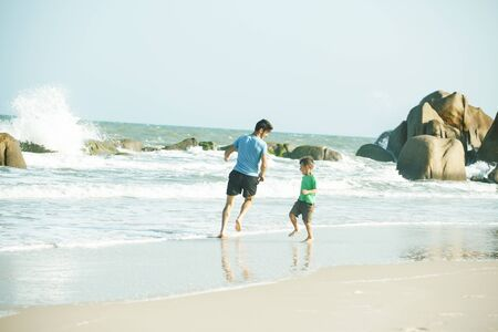 happy family on beach playing, father with son walking sea coast, rocks behind smiling taking vacation