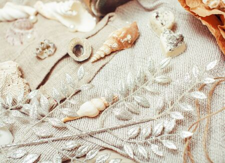 a lot of sea theme in mess like shells, candles, perfume, girl stuff on linen, pretty textured post card view vintage close up