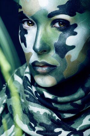 Belle jeune femme à la mode avec des vêtements de style militaire et du maquillage pour le visage, couleurs kaki, célébration d'halloween Banque d'images