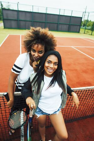 young pretty girlfriends hanging on tennis court, fashion stylish dressed swag, best friends happy smiling together
