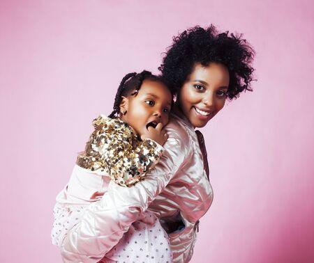 小さなかわいい娘の抱擁を持つ若いかわいいアフリカ系アメリカ人の母親、ピンクの背景に幸せな笑顔、ライフスタイル現代人の概念 写真素材