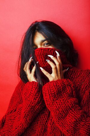 young pretty indian girl in red sweater posing emotional, fashion hipster teenage, lifestyle people concept close up