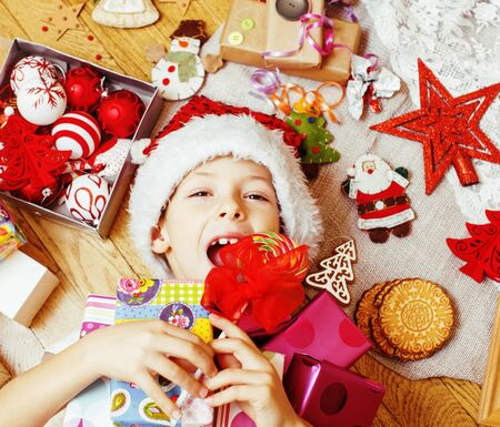little cute boy with Christmas gifts at home. close up emotional happy smiling in mess with toys, lifestyle holiday people concept