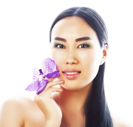 young pretty asian woman with flower purple orchid close up isolated spa, womans day concept