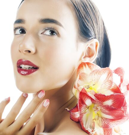 young pretty brunette real woman with red flower amaryllis close up isolated on white background. Fancy fashion makeup, bright lipstick, creative Ombre manicured nails Imagens