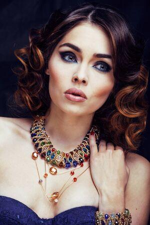 Schönheitsreiche Frau mit hellem Make-up, die Luxusschmuck trägt, sieht aus wie reife Nahaufnahme, lockige Frisur der Modedame