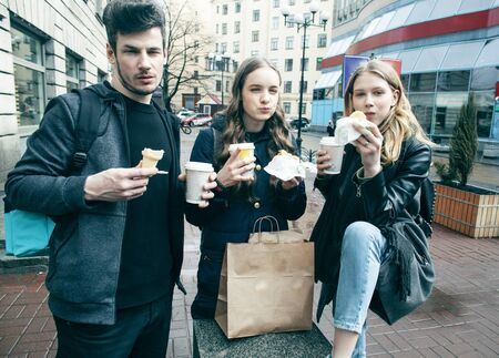 lifestyle and people concept: two girls and guy eating fast food on city street together having fun, drinking coffee Imagens