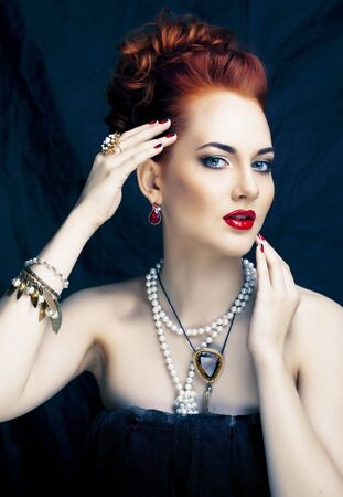 beauty stylish redhead woman with hairstyle and manicure wearing jewelry pearl close up Imagens