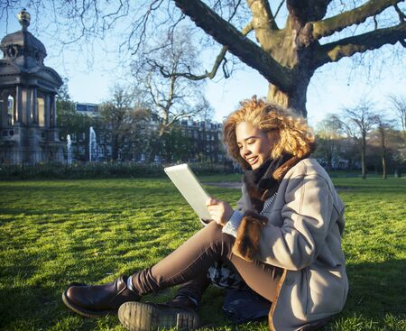 young pretty african american girl with curly hair making photo on a tablet, lifestyle people concept, tourist in european green park Reklamní fotografie