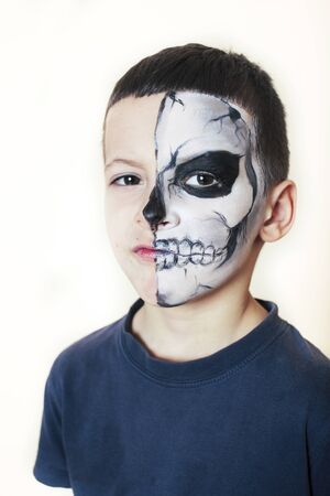 little cute boy with face paint like skeleton to celebrate halloween, lifestyle people concept