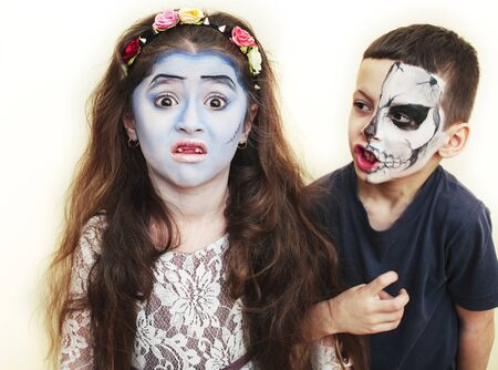zombie apocalypse kids concept. Birthday party celebration facepaint on children dead bride, and skeleton boy and girl couple together having fun, hallooween people