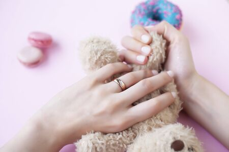 woman hands with manicure wearing wedding ring holdind teddy bear and macaroons on pink background