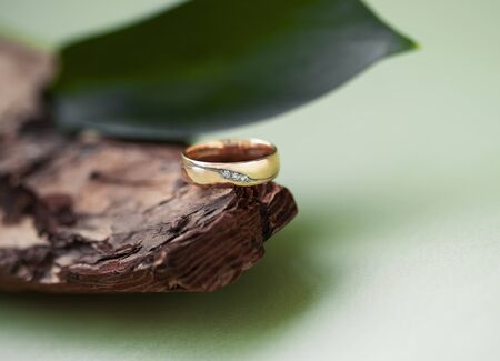 beautiful macro shot of golden wedding ring with some stuff on colored background