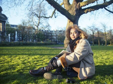 young pretty african american girl with curly hair making photo on a tablet, lifestyle people concept, tourist in european green park Banco de Imagens