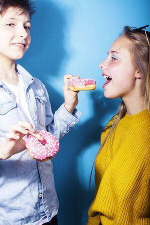 happy family brother and sister eating donuts on blue background, lifestyle people concept, boy and girl eating unhealthy food