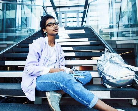 young cute indian girl at university building sitting on stairs reading a book, wearing hipster glasses, lifestyle people concept close up Stockfoto
