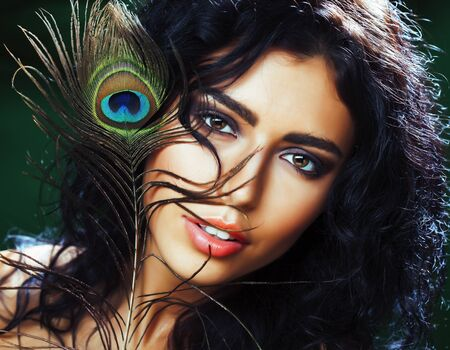 young sensitive brunette woman with peacock feather eyes close up on green smiling, lifestyle people concept macro