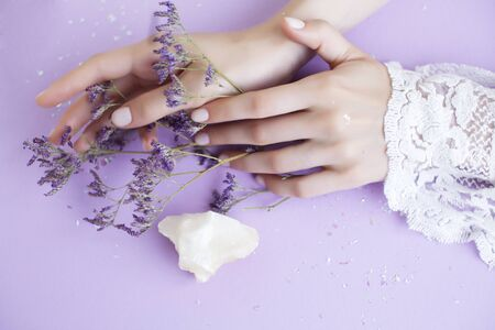 pretty perfect woman hands with white manicure and little flowers on colorful background