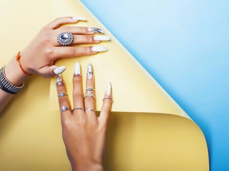 woman hands holding colorful paper copyspace wearing a lot of jewelry and long nails closeup Stock fotó