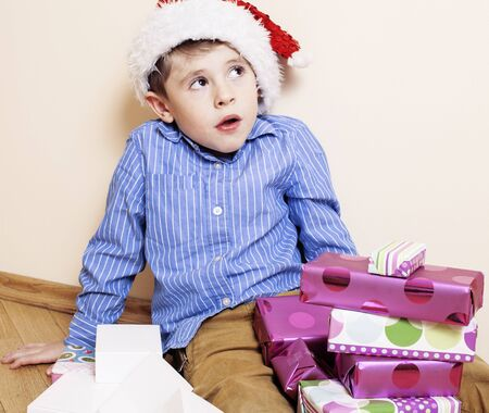 little cute boy with Christmas gifts at home. close up emotional face on boxes in santas red hat, lifestyle people concept