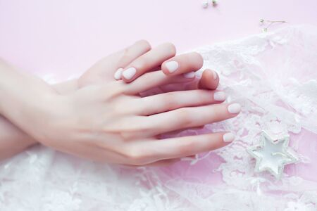 woman hands with manicure among white lace on pink background, cosmetic concept Standard-Bild - 129463393