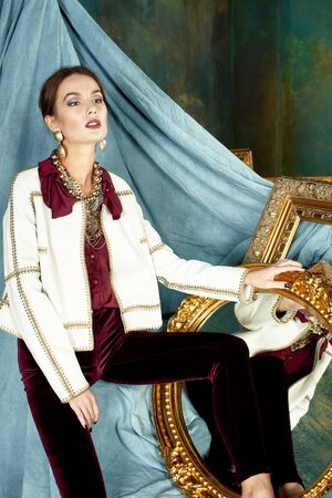 beauty rich brunette woman in luxury interior near empty frames, wearing fashion clothes, lifestyle pretty real people concept Standard-Bild - 129463676