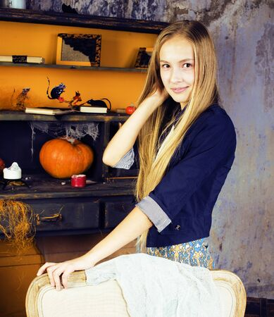 young pretty teenage girl in halloween holiday decorated interior happy smiling, lifestyle people concept