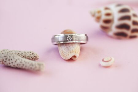 beautiful macro shot of golden wedding ring with sea shell and little flowers on colored background Standard-Bild - 129465076