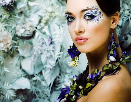 floral face art with anemone in jewelry, sensual young brunette woman in studio close up
