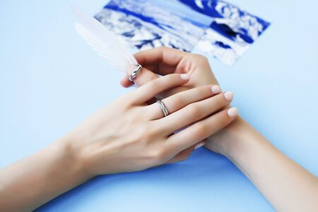 beautiful manicured woman hands with white feather on blue background 写真素材