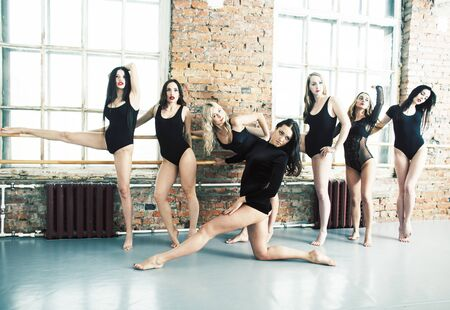 Many girls training in studio ballet, long woman legs sexy bracing, wearing sexual black bodysuit, lifestyle people concept Stock Photo - 129620632