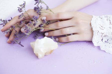 pretty perfect woman hands with white manicure and little purple flowers on lilac background, spa cosmetic concept