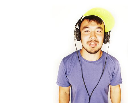 young asian man in hat and headphones listening music on white background Фото со стока