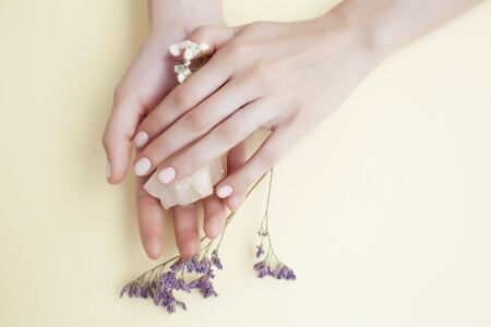 pretty perfect woman hands with white manicure and little flowers on yellow background