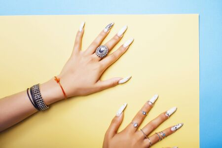 woman hands holding colorful paper copyspace wearing a lot of jewelry and long nails closeup Фото со стока