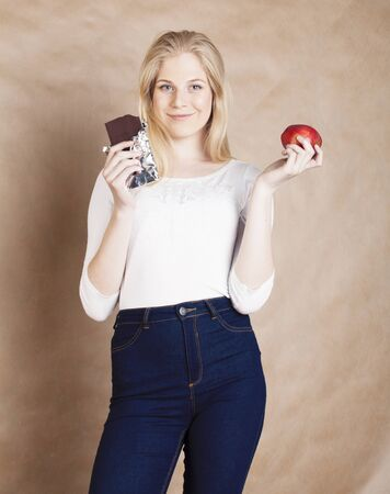 young beauty blond teenage girl eating chocolate smiling, choice between sweet and apple Stock Photo