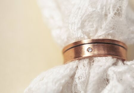 beautiful macro shot of golden wedding ring with some lace on yellow background closeup